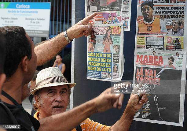 Flamengo's supporters argue next to a kiosk showing newspapers with news and pictures on their covers about Flamengo's football player Ronaldinho...