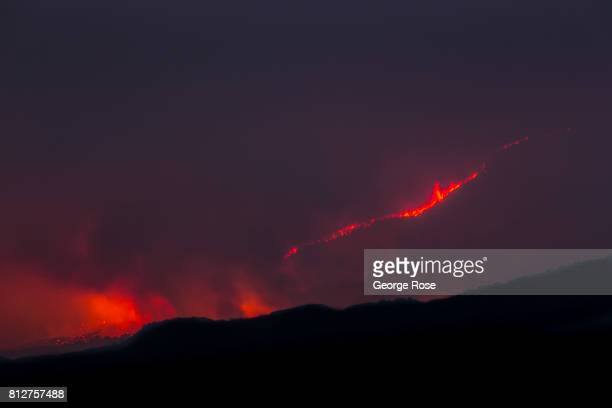 Flames and billowing late afternoon smoke officially called the Whittier Fire burns in the coastal mountains creating an eerie scene on July 8 near...