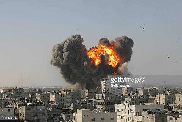 Flames and debris rise following an Israeli air strike on January 13, 2009 in Rafah, Gaza Strip. Israel is intensifying its wide-scale ground assault...