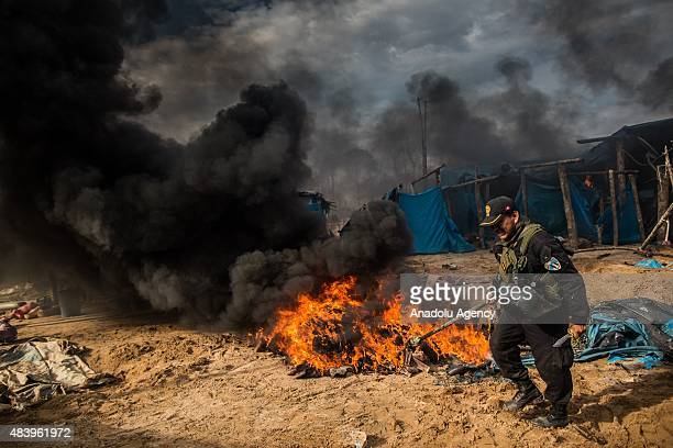 Flames and plumes of black smoke rise over an illegal gold mining camp after authorities set fire to machinery and gasoline used by the miners during...