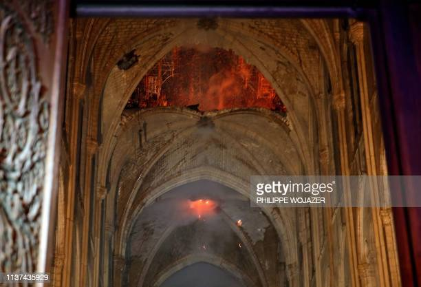 TOPSHOT Flames and smoke are seen as the interior of the NotreDame Cathedral continues to burn on April 15 in the French capital Paris A huge fire...
