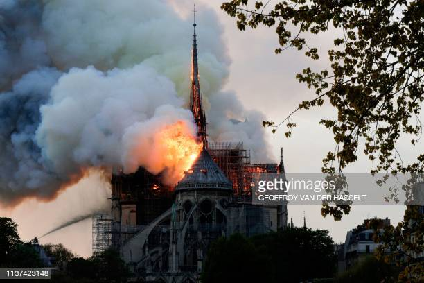 Flames and smoke are seen billowing from the roof at Notre-Dame Cathedral in Paris on April 15, 2019. - A fire broke out at the landmark Notre-Dame...