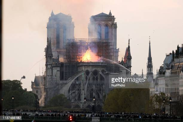 Flames and smoke are seen billowing from the roof at NotreDame Cathedral in Paris on April 15 2019 A fire broke out at the landmark NotreDame...
