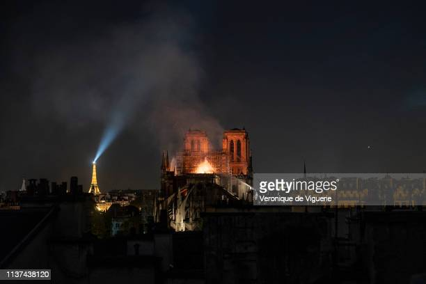 Flames and smoke are seen billowing from the roof at NotreDame Cathedral on April 15 2019 in Paris France A fire broke out on Monday afternoon and...