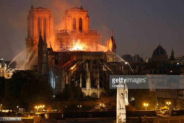 Flames and smoke are seen billowing from the roof at Notre-Dame Cathedral on April 15, 2019 in Paris, France. A fire broke out on Monday afternoon...