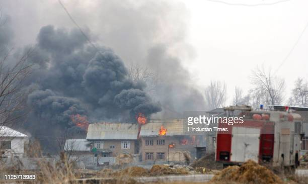 Flames and smoke billows from residential building where militants had taken refuge during a gun battle in Pingilana village of south Kashmir's...
