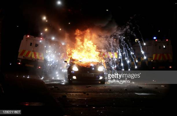 Flames and smoke rise from car set a fire during protests as rioters hurled petrol bombs, fireworks and stones at police amid unrest since Wednesday,...