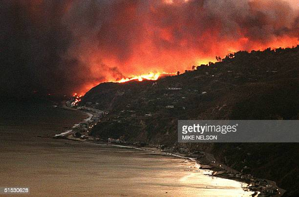 Flames and smoke rise on the hillside above Malibu early 03 November 1993 after a wildfire burned through the area late 02 November burning over 200...