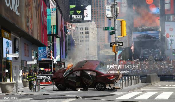 Flames and smoke rises from a wrecked vehicle after it plowed into pedestrians on a busy sidewalk on the corner of West 45th St and Broadway at Times...