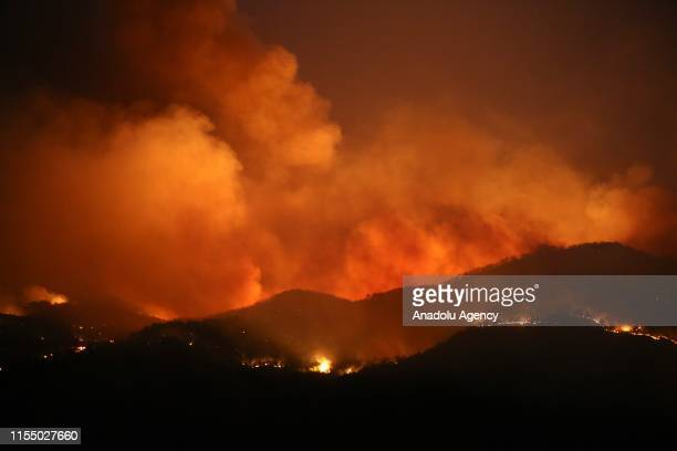 Flames and smoke rising as firefighters try to extinguish the fire that broke out at a forest in Mugla's Dalaman district Turkey on July 11 2019 Fire...
