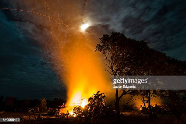 Flames and sparks fly into the air as a farmer burns surplus timber in a bonfire on his farm during winter.