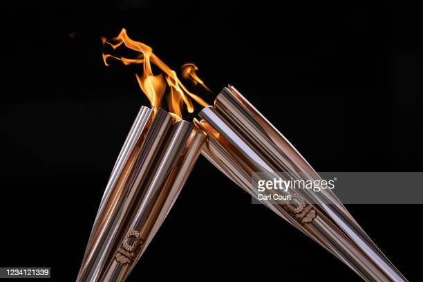Flames are exchanged during the arrival ceremony for the Olympic torch on July 23, 2021 in Tokyo, Japan.