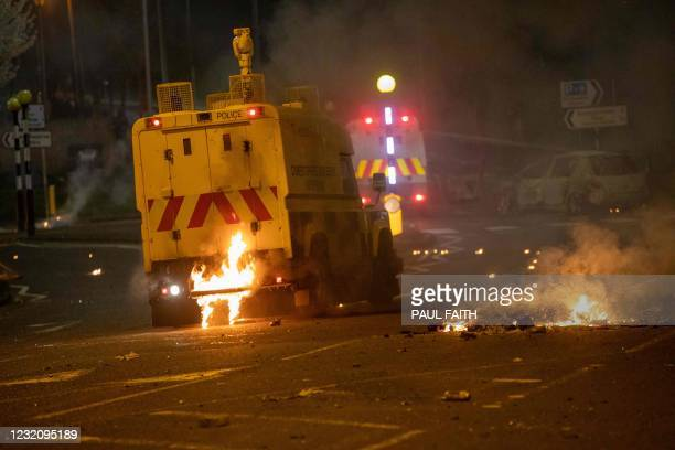 Flames are seen at the rear of a police vehicle after violence broke out in Newtownabbey, north of Belfast, in Northern Ireland on April 3, 2021. -...