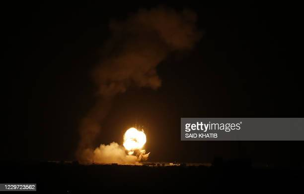 Flames are seen following an Israeli air strike in the town of Khan Yunis in the southern Gaza Strip early on November 22 2020 A rocket was fired at...