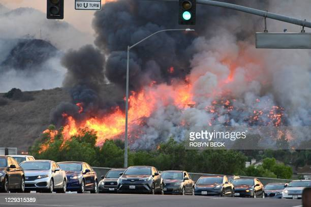 Flames are seen in the background as vehicles drive on a highway overpass at the Blue Ridge Fire in Chino, California, October 27, 2020. - Two...