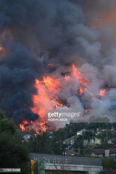Flames are seen near homes off the 71 freeway at the Blue Ridge Fire in Chino, California, October 27, 2020. - Two wind-driven wildfires in southern...