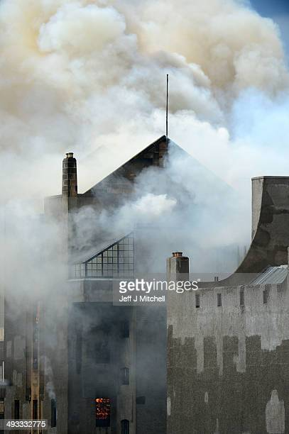 Flames are seen through a window as smoke rises into the sky after a fire broke out at the Glasgow School of Art Charles Rennie Mackintosh Building...