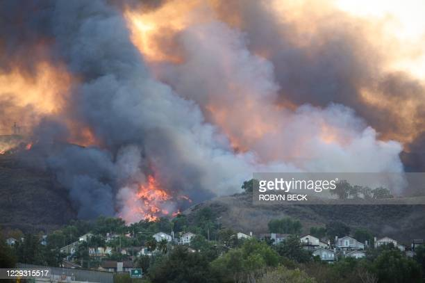 Flames are seen through the dense smoke near homes off the 71 freeway at the Blue Ridge Fire in Chino, California, October 27, 2020. - Two...