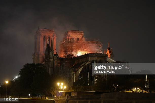 Flames are seen through the scaffolding as they engulf the roof of the NotreDame Cathedral in Paris on April 15 2019 A colossal fire swept through...