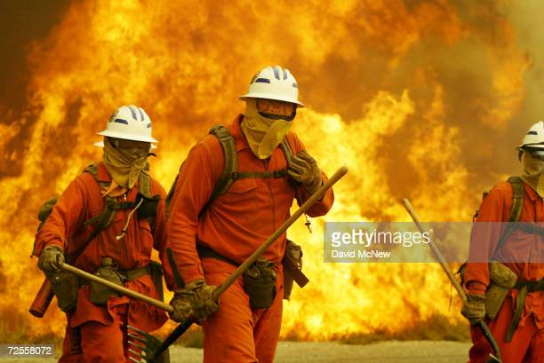 Flames boil up behind a probation camp hand crew members as the Foothill Fire takes off on July 17, 2004 near Santa Clarita, California. The Foothill...