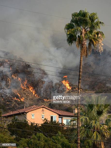 Flames burn near a home during the Colby Fire January 16 2014 in Azusa California The fastmoving Colby Fire originated early on Thursday in the San...