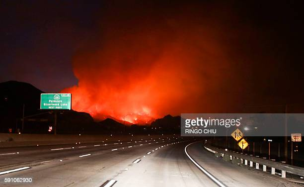 Flames burn next to the Interstate 15 as the Blue Cut wildfire rages near Cajon Pass north of San Bernardino California on August 16 2016 A rapidly...
