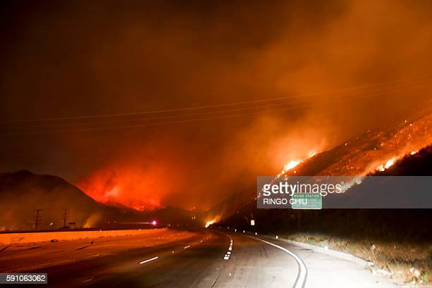TOPSHOT Flames burn next to the Interstate 15 as the Blue Cut wildfire rages near Cajon Pass north of San Bernardino California on August 16 2016 A...