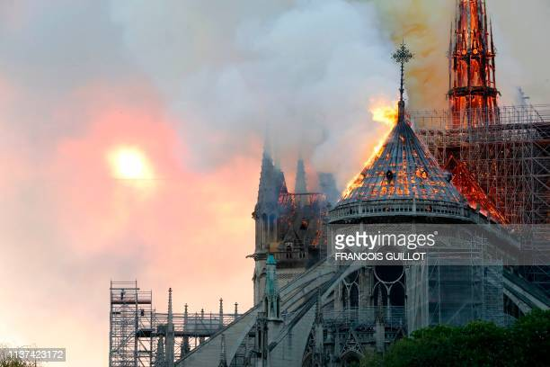 Flames burn the roof of the landmark NotreDame Cathedral in central Paris on April 15 2019 A major fire broke out at the landmark NotreDame Cathedral...