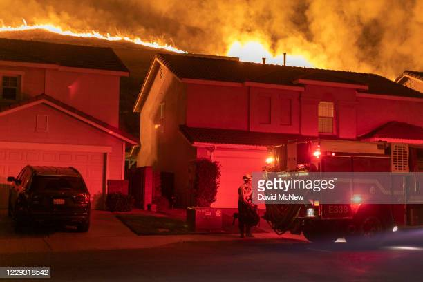 Flames come close to houses during the Blue Ridge Fire on October 27, 2020 in Chino Hills, California. Strong Santa Ana Winds gusting to more than 90...