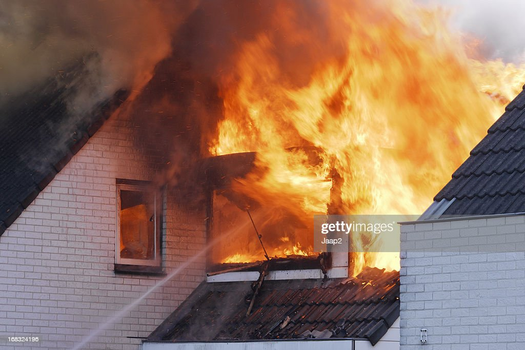 Flames coming out of white brick wall house on fire : Stock Photo