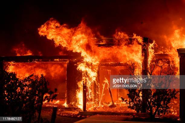 Flames consume a home during the Kincade fire as flames race through Healdsburg California on October 27 2019 Powerful winds were fanning wildfires...