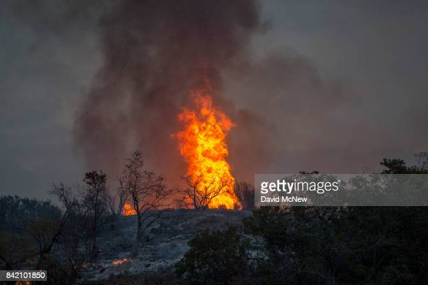 Flames creep down from a ridge and toward homes after sunset at the La Tuna Fire on September 2 2017 near Burbank California Los Angeles Mayor Eric...