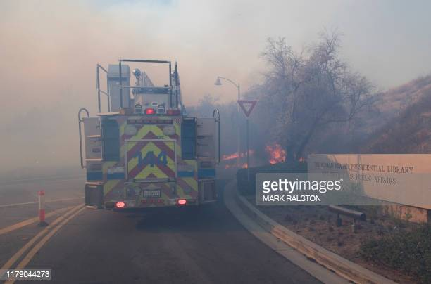 Flames cross the driveway of the Reagan Library as firefighters battle to protect it from the Easy Fire in Simi Valley California on October 30 2019...