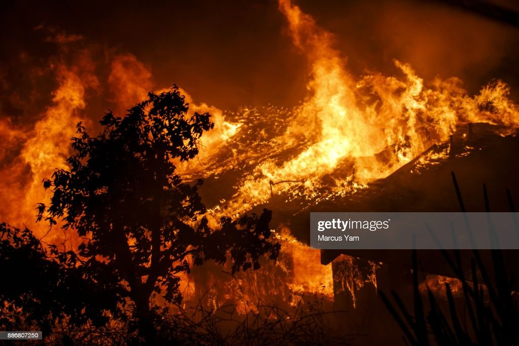 Flames engulf a home as brush fire sweeps through the area threatening structures on December 5, 2017 in Oakview, California.