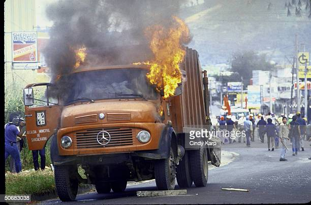 Flames engulfing vehicle set afire by students workers peasants who are protesting assassination of Human Rights Comm president Herbert Anaya Sanabria