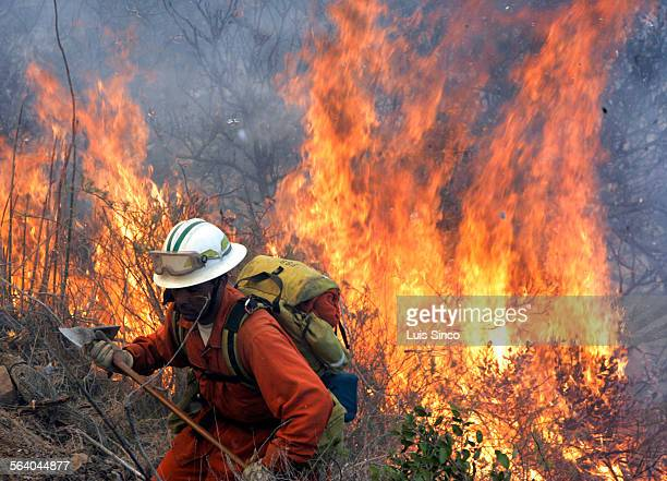 Flames flare behind a California Department of Corrections hand crew member along Airport Road on Catalina Island