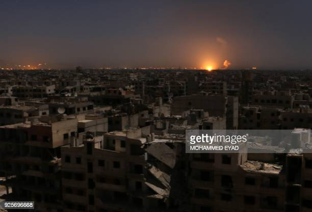 Flames following a reported rocket attack is seen on the horizon in the rebel-held enclave of Eastern Ghouta on February 28, 2018. / AFP PHOTO /...