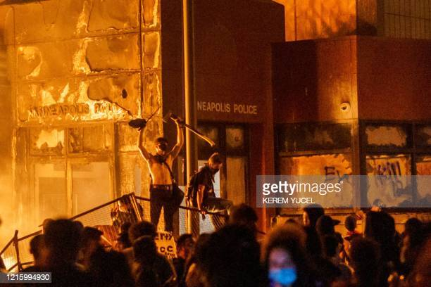 TOPSHOT Flames from a nearby fire illuminate protesters standing on a barricade in front of the Third Police Precinct on May 28 2020 in Minneapolis...
