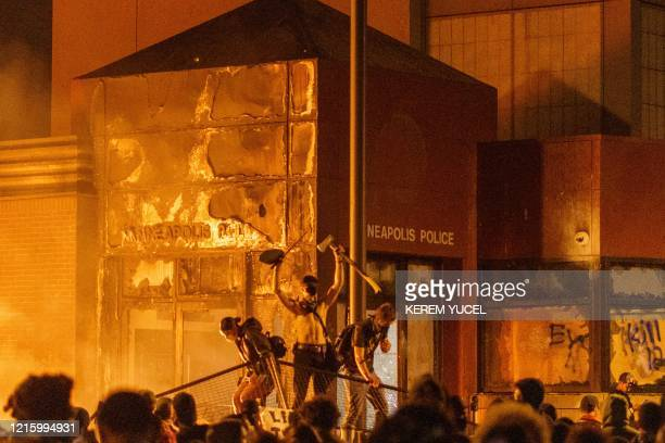 Flames from a nearby fire illuminate protesters standing on a barricade in front of the Third Police Precinct on May 28, 2020 in Minneapolis,...