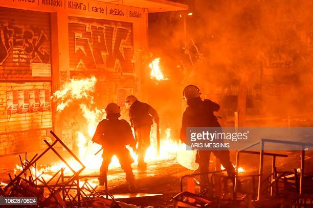Flames from petrol bombs burn after exploding close to anti-riot police officers in downtown Athens on November 17 during clashes following a rally...