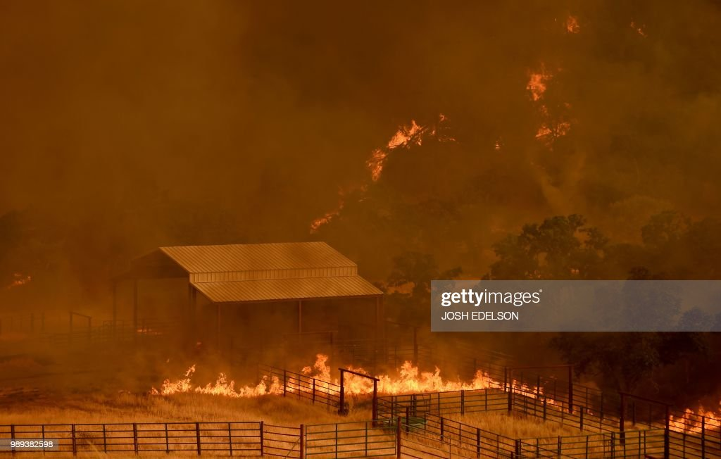 Flames from the County Fire move through a property in Guinda, California, on July 1, 2018. - Californian authorities have issued red flag weather warnings and mandatory evacuation orders after a series of wildfires fanned by high winds and hot temperatures ripped through thousands of acres. The latest blaze, the County Fire sparked in Yolo County on June 30, had by July 1 afternoon spread across 22,000 acres (9,000 hectares) with zero percent containment, according to Cal Fire.