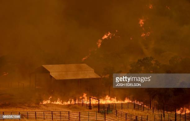 Flames from the County Fire move through a property in Guinda California on July 1 2018 Californian authorities have issued red flag weather warnings...