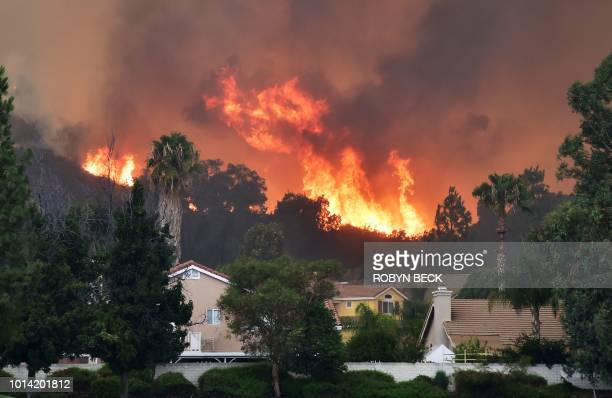 TOPSHOT Flames from the Holy Fire shoot up above homes in Lake Elsinore California southeast of Los Angeles on August 9 2018 A man suspected of...