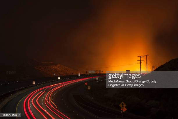 Flames glow as traffic drives north on the 15 Freeway seen from the Highway 138 overpass after it was reopened Wednesday night as firefighters...
