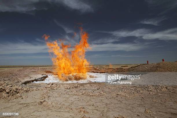 Flames leap up from a pond which formed during a 1980s drilling exploration in the Karakum Desert on May 20 2016 in Lebap Turkmenistan The fire in...