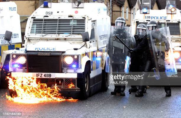 Flames lick up the front of a police vehicle as police officers are attacked by nationalist youths in the Springfield Road area of Belfast on April...