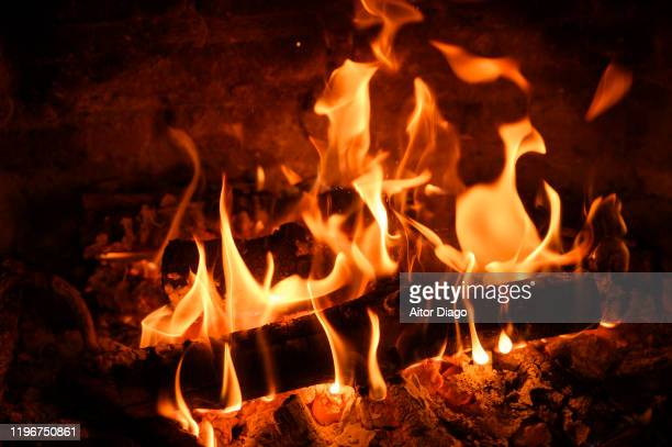 flames of fire are consuming the logs of oak wood which is burning in the fireplace. - 暖炉の火 ストックフォトと画像