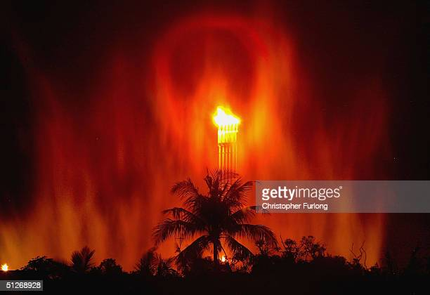 Flames pour from vents and create an eery glow on steam rising out of oil and gas processing facilities at Seria September 7 2004 in Brunei Brunei...