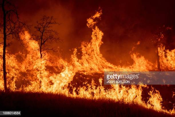 Flames race across a hillside as firefighters monitor a backfire during the Carr fire in Redding California on July 27 2018 One person has died and...