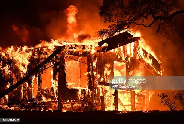 Flames ravage a home in the Napa wine region in California on October 9 as multiple winddriven fires continue to whip through the region / AFP PHOTO...